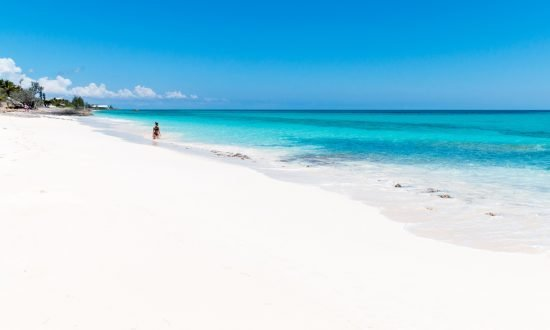 person walking down sandy white beach in abaco