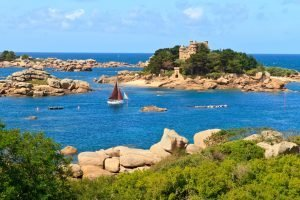 sailboat going to castle on island in brittany