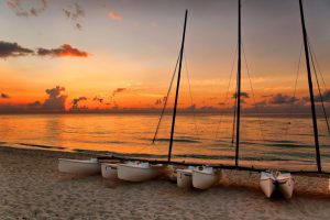 boats on the beach at sunset