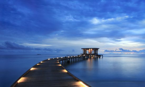 long dock with lights at night in maldives