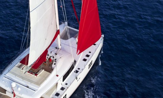 aerial of boat sailing with red sails