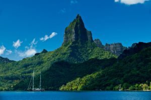tall mountain cliffs and boat in the water