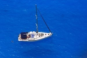 aerial of boat with person swimming behind