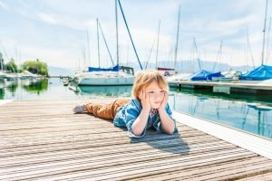 kid chilling on a dock surrounded by boats