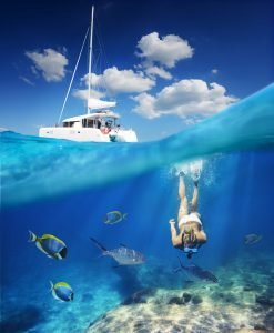 diving under water with fish while boat is on surface of water