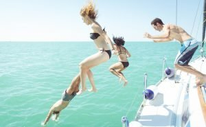 four people jumping off a boat into water
