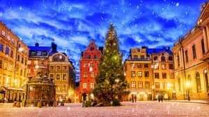 snow falling in the town center with christmas tree