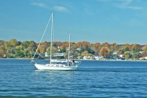 sailboat in the water with leaves changing behind