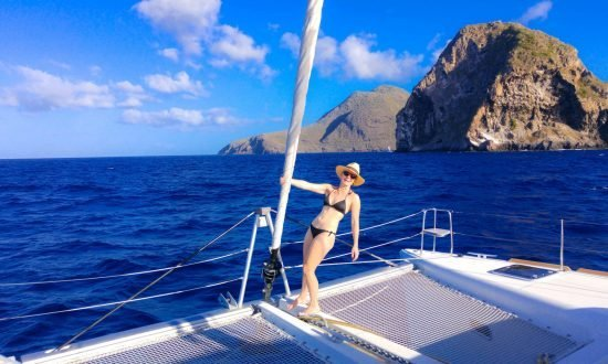 a feminine presenting person posing on a cabin charter boat with a mountain in the distance