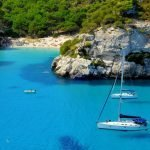 boats passing hidden beach in Balearic Islands