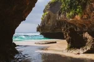 water and beach between two large rocks bali