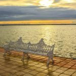 bench on the edge of the water at sunset