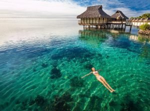 woman floating in the water next to bungalows