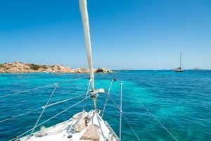 boat approaching rocks in the blue water of sardinia