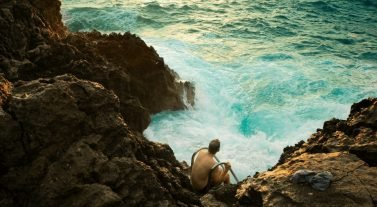 man sitting on rocks edge with waves crashing around rocks