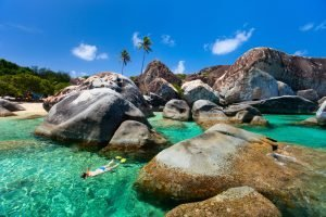 snorkeling around the rocks in the water of the shore of a beach