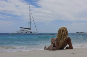 woman relaxing on the beach with a view of the boat