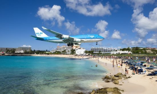 Plane flying over beach with people in St Martin