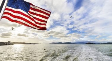 American Flag blowing in the wind off the stern of the boat
