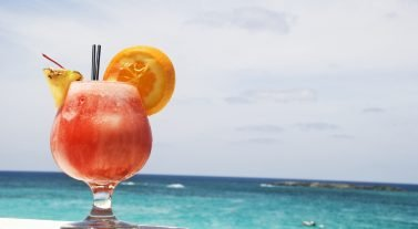 tequila sunrise with a view of the Caribbean Sea