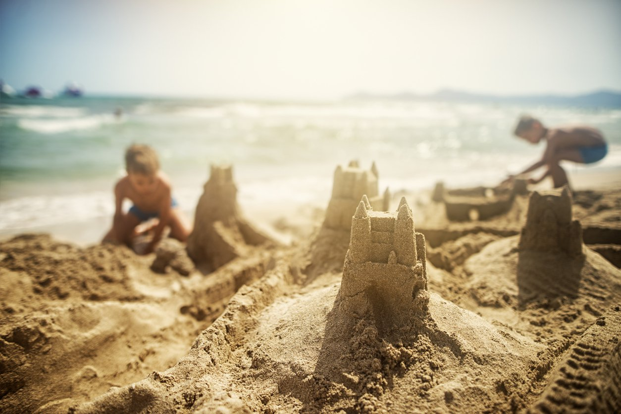 Brothers building sandcastles on the beach